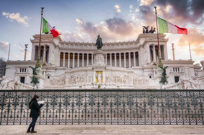 Angolo basso di turista donna in piedi con mappa vicino all'Altare della Patria con Monumento Nazionale Vittorio Emanuele II durante le vacanze a Roma — Foto stock