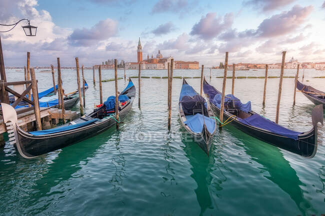 Traditional gondolas moored on rippling water surface on background of city and sundown sky in Venice — Stock Photo