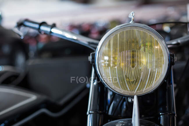 Closeup of yellow headlight of old fashioned motorbike placed against blurred background of workshop — Stock Photo