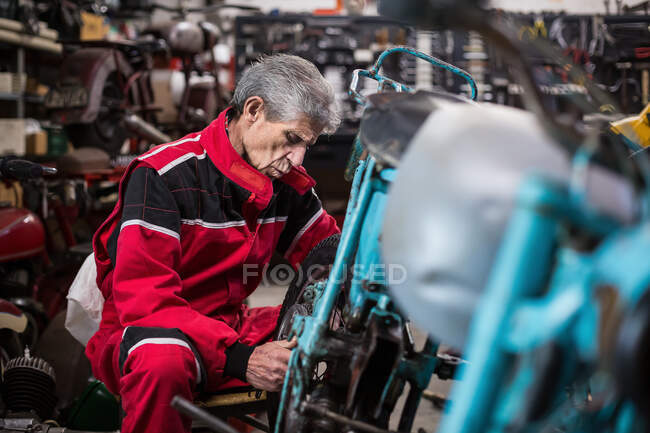 Side view of serious skilled elderly male mechanic in workwear repairing old fashioned broken motorcycle and fixing wheel in workshop — Stock Photo