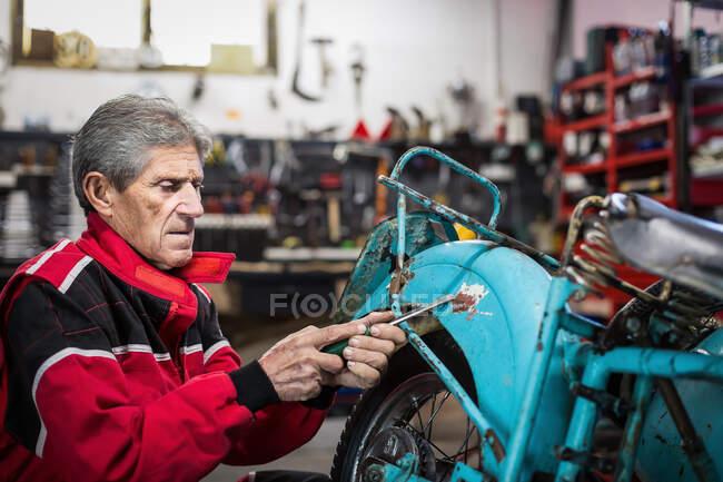 Сторона зору літнього сірого чоловіка механіка з викруткою видалення бруду і іржі з розбитого мотоцикла ретро під час роботи в гаражі. — стокове фото
