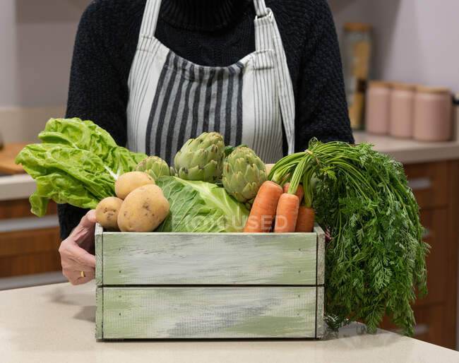 Crop unrecognizable senior female in apron standing at table with box full of fresh ripe vegetables in kitchen — Stock Photo