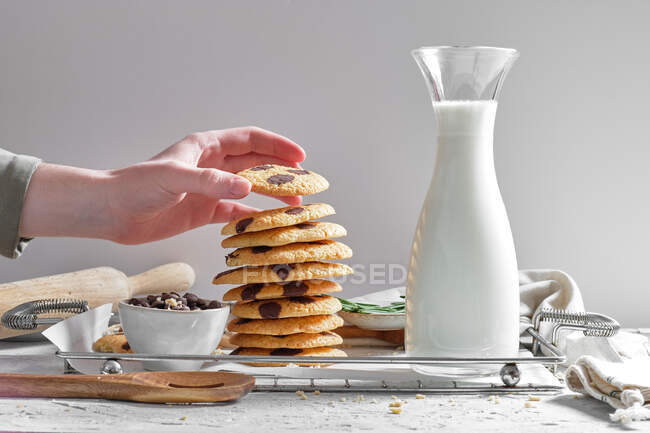 Crop anonymous housewife stacking delicious homemade cookies with chocolate chips on tray with jar of fresh milk in kitchen — Stock Photo