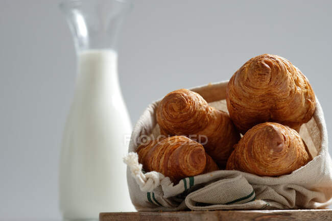 Delicious croissants and bottle of milk placed on table for breakfast in kitchen — Stock Photo