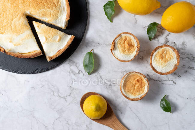 From above of sweet meringue pie and fresh lemons arranged on marble table in kitchen — Stock Photo