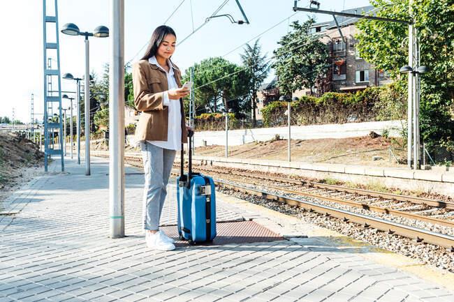 Вміст етнічної жінки-мандрівника стоїть з валізою на платформі на залізничній дорозі і переглядає смартфон. — стокове фото