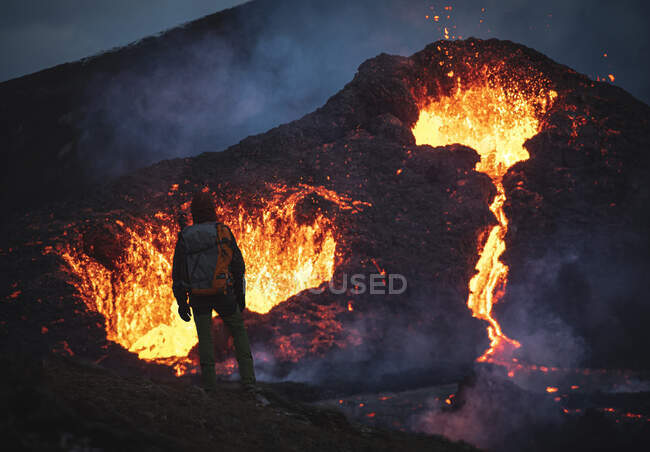 Man explorer observing the magma sparks out of the volcano Fagradalsfjall in Iceland between clouds of smoke — Stock Photo