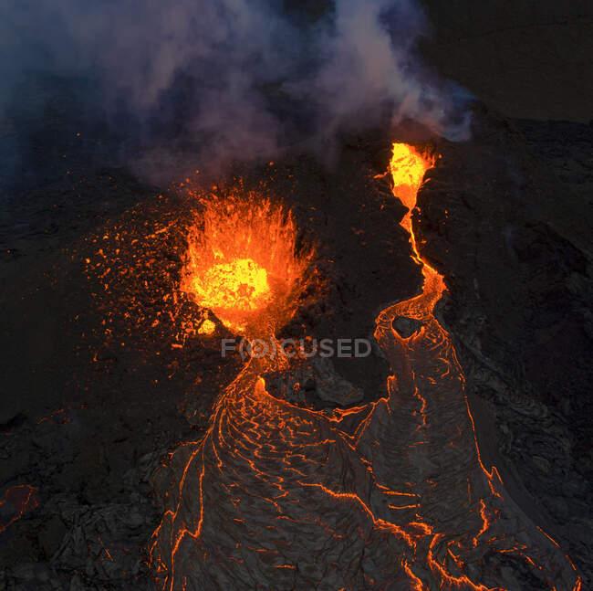 Desde arriba el magma sale del agujero del volcán y corre como ríos de lava sobre el suelo en Islandia - foto de stock