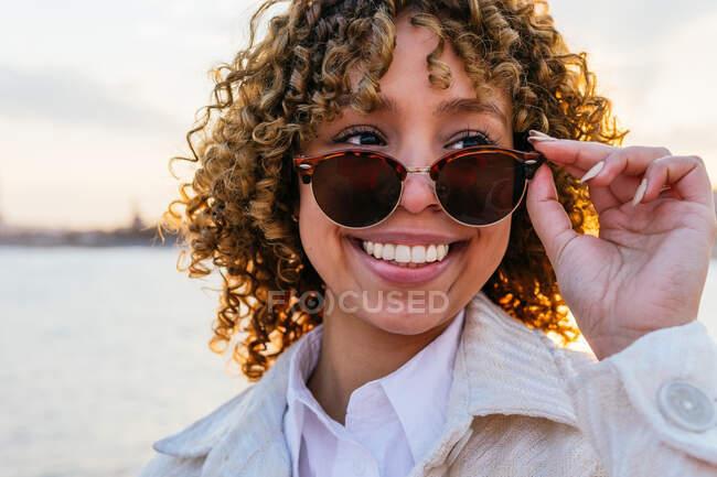 Веселий афроамериканець на розкішних сонцезахисних окулярах стоїть на березі і насолоджується свободою на заході сонця, озираючись — стокове фото