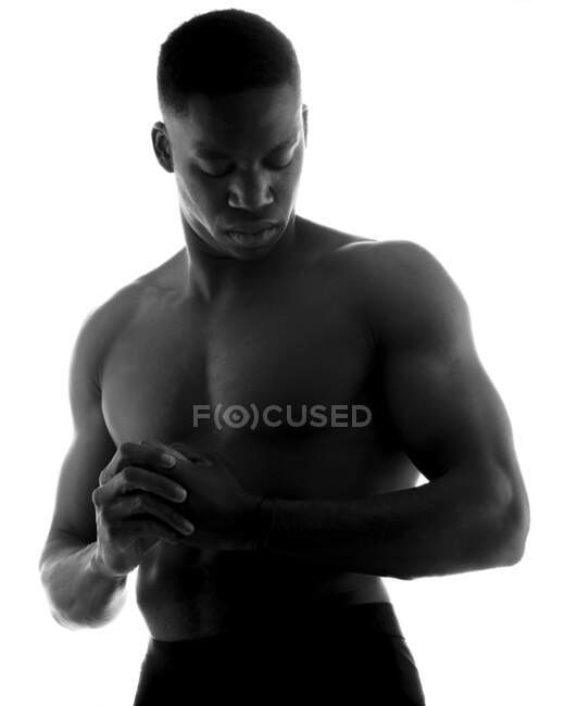 Black and white of unemotional shirtless muscular young black man with folded hands and closed eyes in studio on white background — Stock Photo
