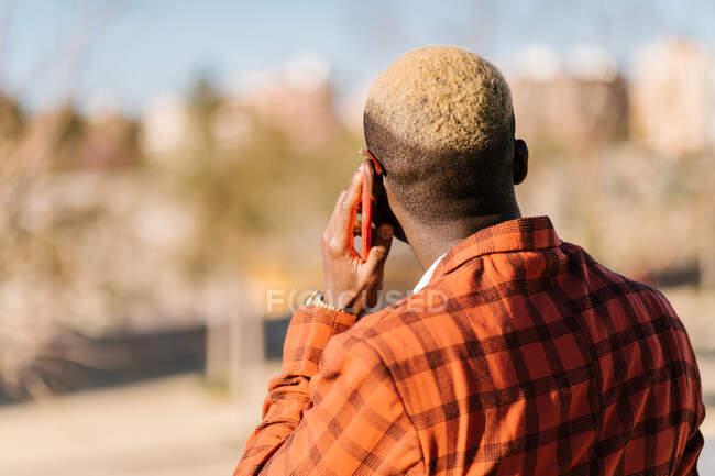 Visão traseira de macho preto na moda irreconhecível com cabelo tingido de loiro em terno xadrez e óculos falando no telefone celular enquanto olha para longe à luz do sol — Fotografia de Stock