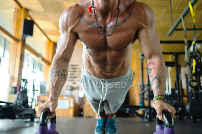 Ground level of crop unrecognizable shirtless male athlete doing push ups on kettlebells during functional workout in spacious gym — Stock Photo
