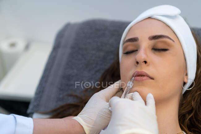 De arriba del cultivo el esteticista profesional irreconocible con la jeringa que inyecta el relleno con el ácido hialurónico en los labios del cliente femenino durante el procedimiento en la clínica de belleza - foto de stock