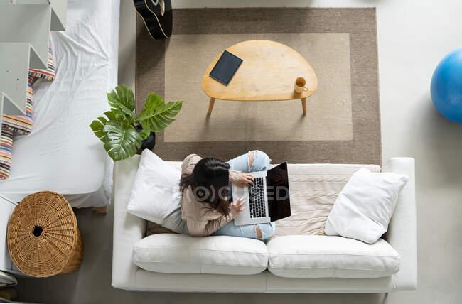Високий кут анонімної жінки, яка переглядає Інтернет на портативному комп'ютері з чорним екраном, відпочиваючи на дивані вдома. — стокове фото