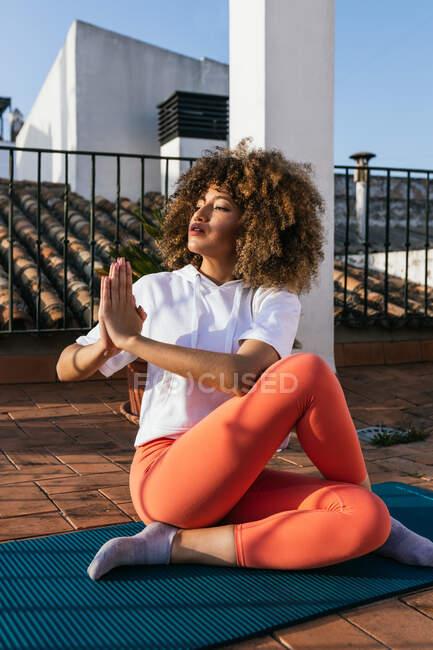 Этническая женщина в спортивной одежде сидит со скрещенными ногами и руками намасте, практикуя йогу и глядя на крышу дома — стоковое фото