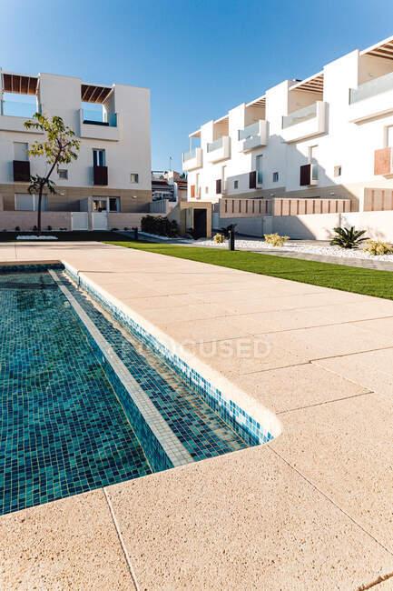 Casa contemporânea exteriores contra piscina com água ondulada e gramado sob céu azul na cidade — Fotografia de Stock
