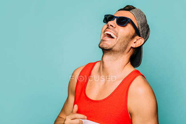 Cheerful young bearded man wearing trendy casual striped shirt and cap with black sunglasses on blue background — Stock Photo