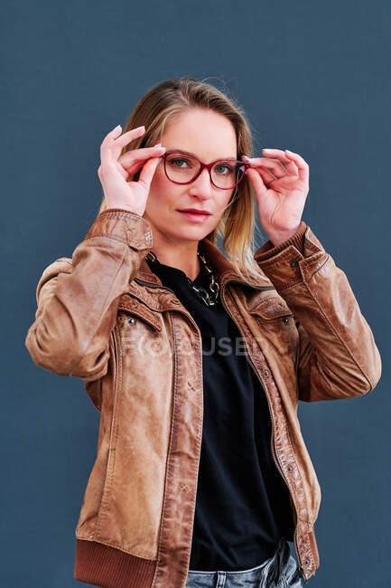 Самовпевнена доросла жінка в шкіряній куртці і окуляри дивлячись на камеру в денний час — стокове фото