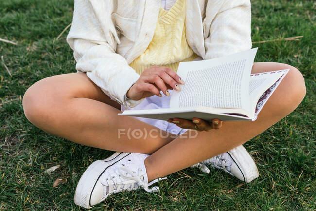 Вроджена незнайома жінка сидить в парку і читає цікаву книжку влітку. — стокове фото