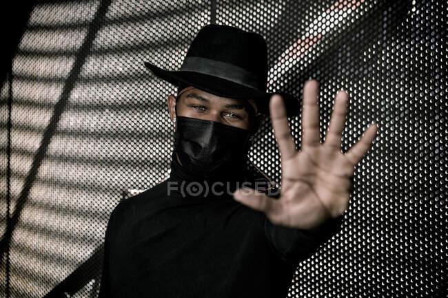 Black male in trendy hat and protective mask showing stop sign while standing in underground parking and looking at camera — Stock Photo