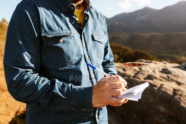Vista lateral de la cosecha irreconocible explorador masculino de pie en la colina en las montañas y la escritura en bloc de notas durante las vacaciones - foto de stock
