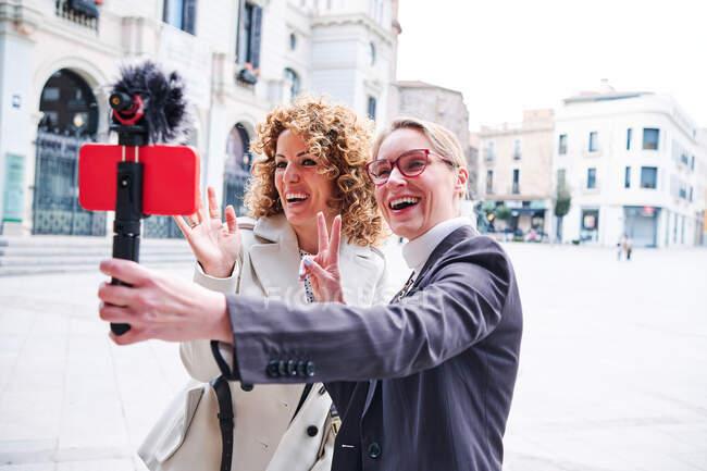 Felices novias saludando de la mano y mostrando el gesto de victoria mientras toma autorretrato en el teléfono celular en la ciudad - foto de stock