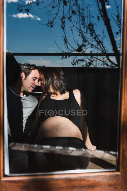Через вікно вагітної жінки і задоволений чоловік ніжно торкається носа в сонячний день вдома. — стокове фото