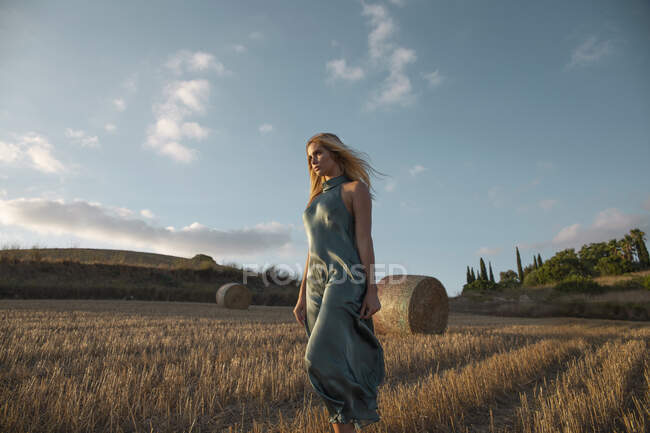 Peaceful female in elegant dress standing on dry field in rural area and looking away — Stock Photo
