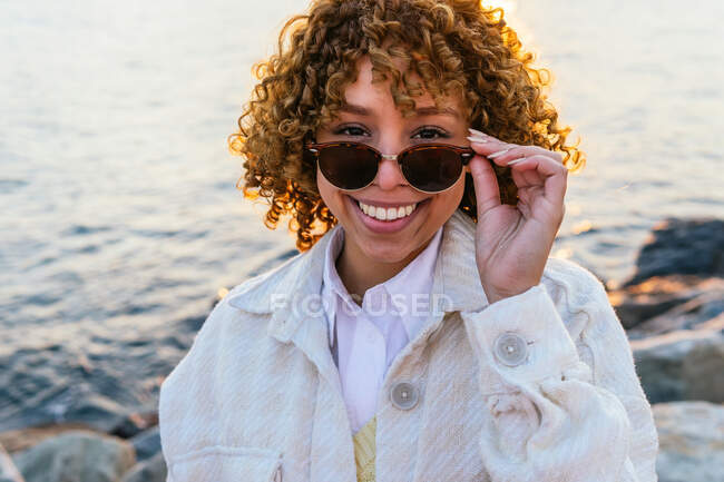 Cheerful African American female on stylish sunglasses standing on seashore and enjoying freedom at sunset looking at camera — Stock Photo
