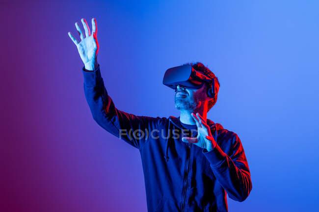 Невпізнаваний бородатий самець в копирці і сучасному начальнику, який досліджує віртуальну реальність в неоновому світлі. — стокове фото