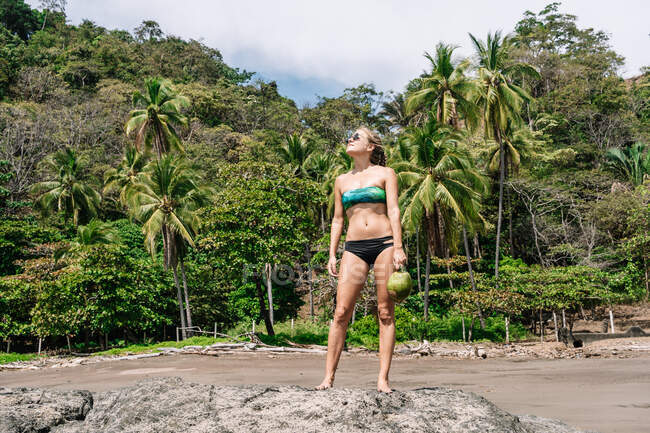 Full body young woman with coconut looking away while standing on stone against palm on sunny day on tropical resort — Stock Photo