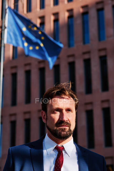 Unshaven dirigente maschile in giacca e cravatta guardando dall'altra parte contro l'edificio a più piani e la bandiera dell'Unione Europea in città — Foto stock