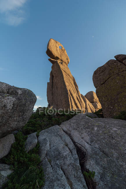 From below of ornamental stone formation located in highlands in Sierra de Guadarrama National Park at blue sky — Stock Photo