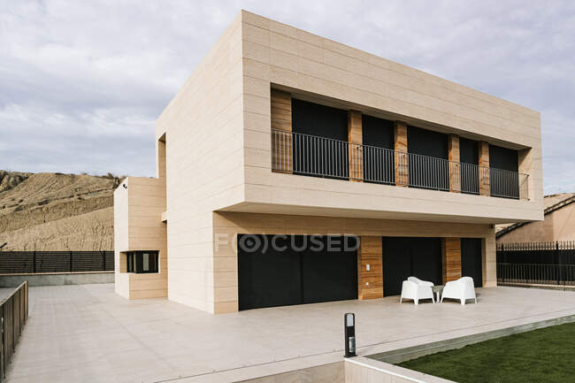 Contemporary masonry building exterior with fenced balcony against mount and walkway under cloudy sky in town — Stock Photo