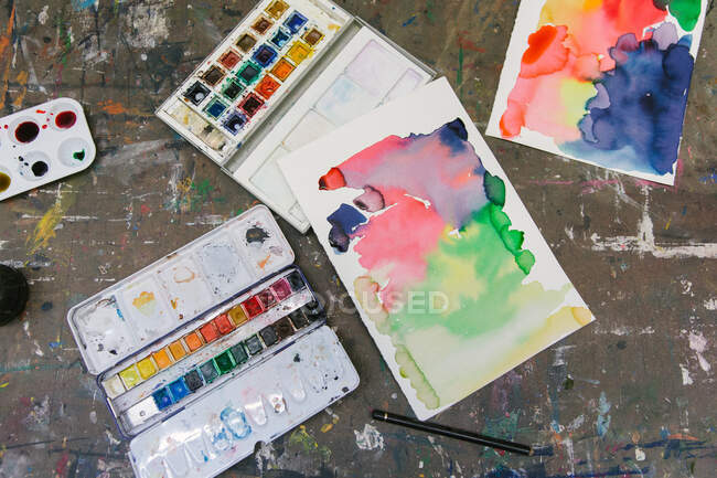 From above of watercolor paint palettes and abstract pictures arranged on table in creative studio — Stock Photo