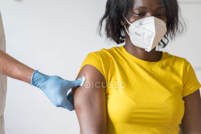 Невпізнаваний чоловік - медик, який займається захистом латексних рукавичок, вакцинує жіночу афроамериканську пацієнтку в клініці під час спалаху коронавірусу. — стокове фото
