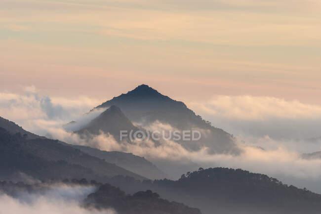Impresionante paisaje de picos montañosos cubiertos de nubes bajo el colorido cielo del atardecer en el Parque Nacional Sierra de Guadarrama - foto de stock