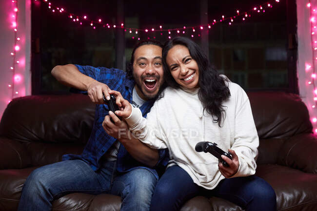 Excited ethnic couple in casual wear with joy pads playing video game together while sitting on leather couch at home — Stock Photo