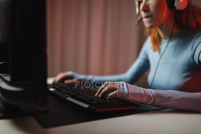 Side view of cropped unrecognizable female gamer in headphones playing videogame while sitting at table at home — Stock Photo