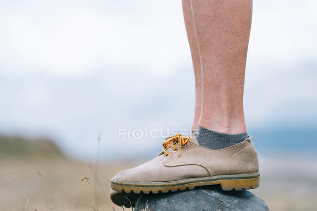 Side view of crop female hiker in boots standing on rock in nature during trekking in summer — Stock Photo