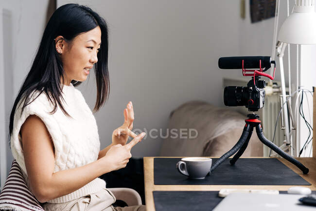 Smiling ethnic female blogger with cup of hot drink talking while recording video on photo camera at home — Stock Photo