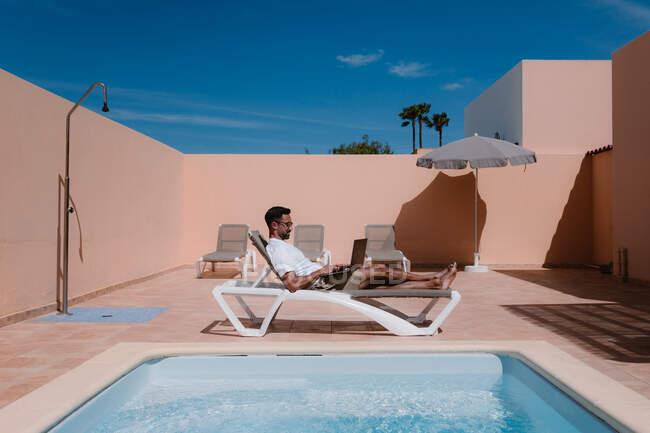 Літом у сонячний день на ноутбуці лежить інший чоловік - фрілансер у вітальні та серфінг Інтернету на ноутбуці. — стокове фото