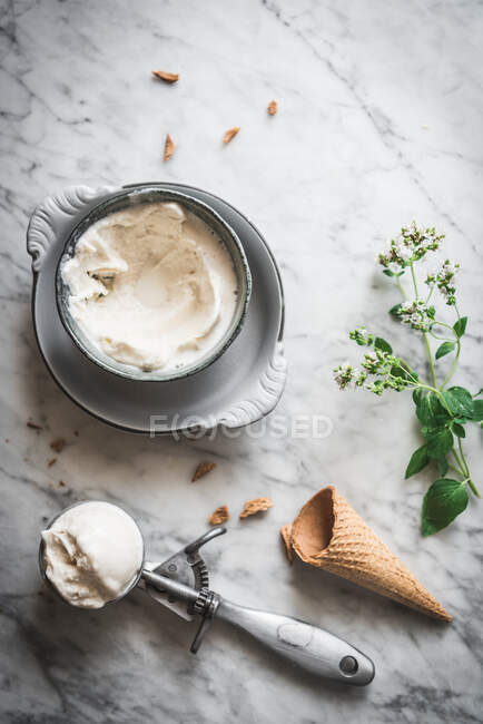 From above of waffle cone near meringue milk gelato scoops and fresh mint leaves on marble table — Stock Photo