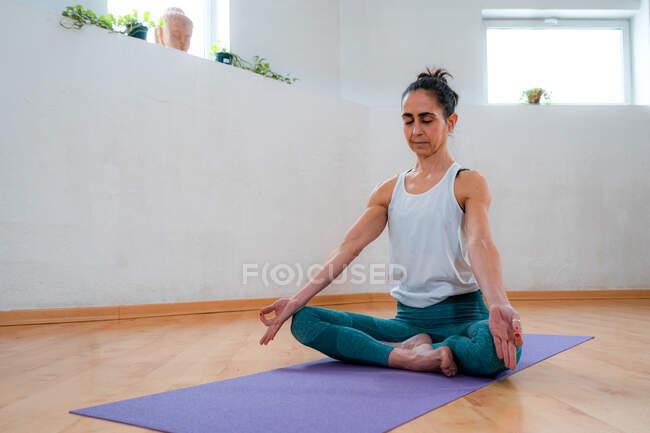 Концентрированная зрелая женщина в спортивной одежде с закрытыми глазами, сидящая на коврике для йоги во время медитации в доме — стоковое фото