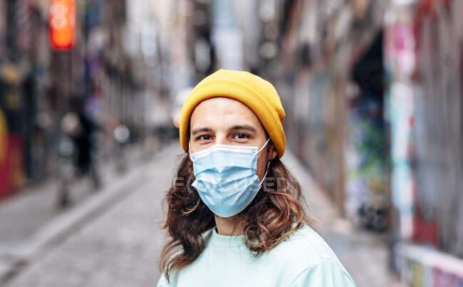 Masculino em chapéu de malha e máscara descartável olhando para a câmera na cidade durante a pandemia COVID 19 — Fotografia de Stock