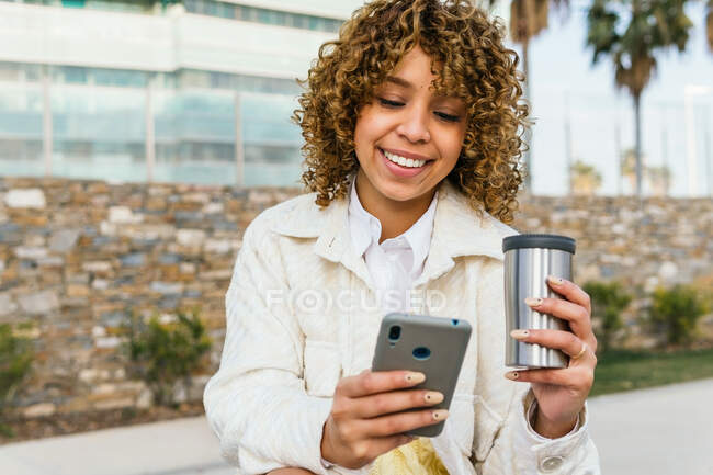 Positive African American female with takeaway coffee messaging on social media via smartphone in street of city — Stock Photo