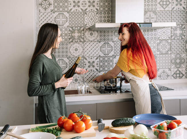 Content young homosexual girlfriends with bottle of wine speaking while looking at each other between stove and fresh vegetables — Stock Photo