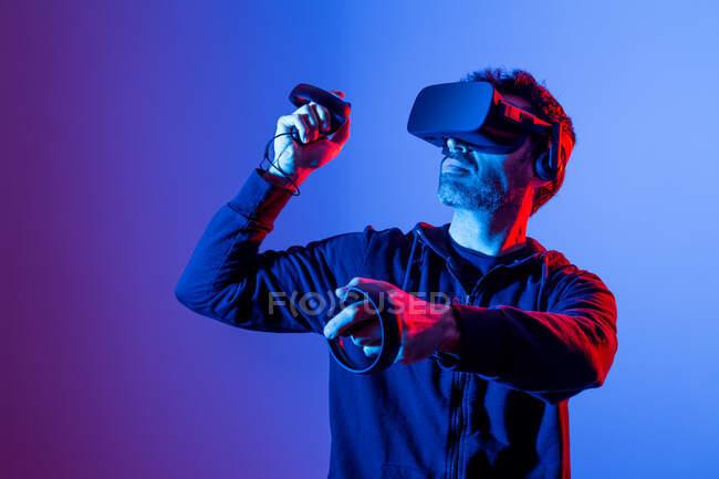 Anónimo hombre sin afeitar en sudadera con capucha y gafas modernas con controladores y brazo extendido experimentando realidad virtual - foto de stock