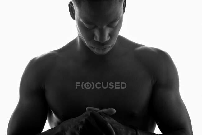 Negro y blanco de hombre negro musculoso sin camisa sin emociones con las manos dobladas y los ojos cerrados en el estudio sobre fondo blanco - foto de stock