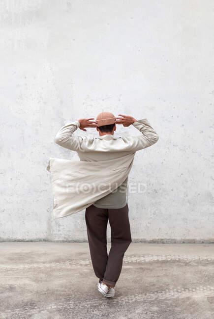 Погляд на анонімного хлопця, який танцює в міській місцевості біля сірої стіни будинку. — стокове фото